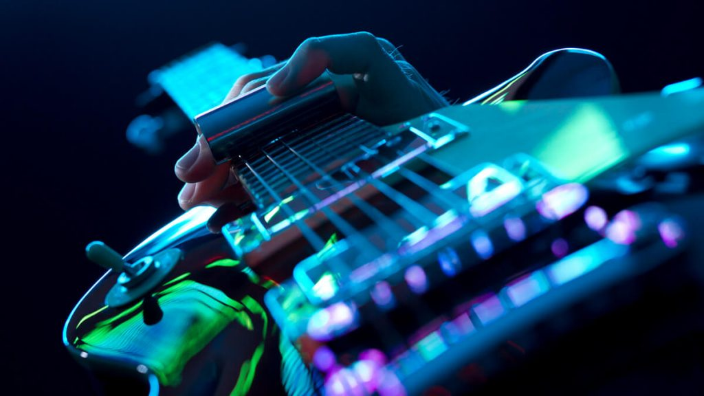 Detalhe da mão de um guitarrista tocando sua guitarra Les Paul com um slide