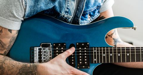 Close em um guitarrista tatuado com uma guitarra azul