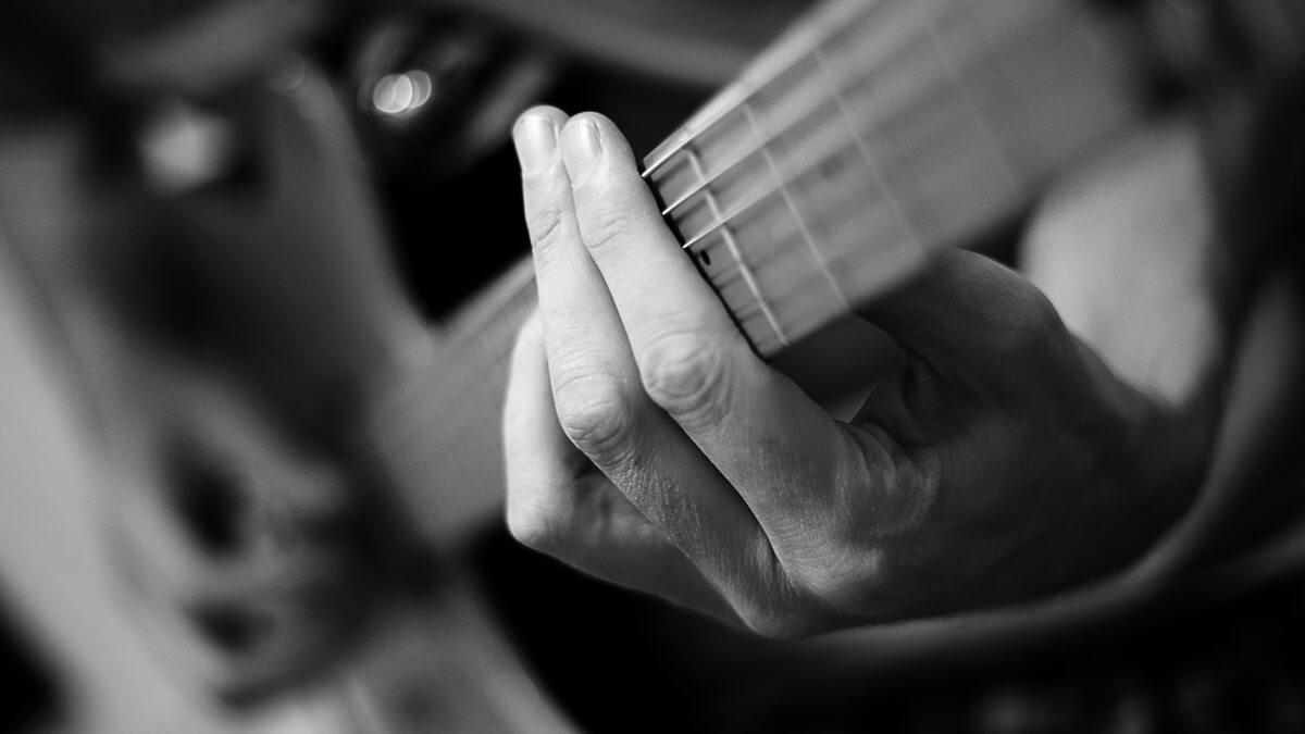 Foto preto e branco com destaque em um Power Chord executado na guitarra